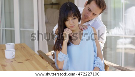 Man trying to comfort sad woman at table