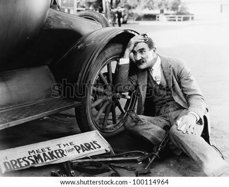 Man trying to fix broken car - stock photo