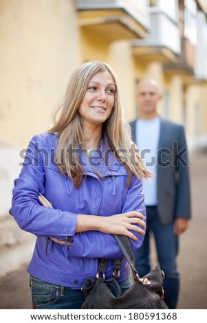 Man trying to get acquainted with woman on city street - stock photo