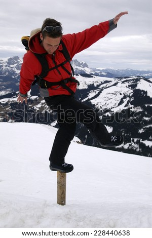 Man trying to keep balance on post