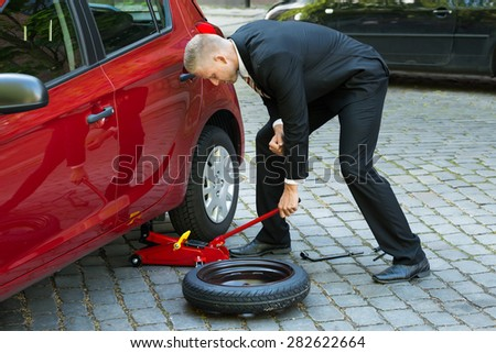 Man Trying To Lift The Car With Red Hydraulic Floor Jack For Repairing - stock photo