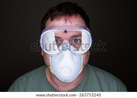 MAn trying to prevent infection with safety goggles and a mask - stock photo