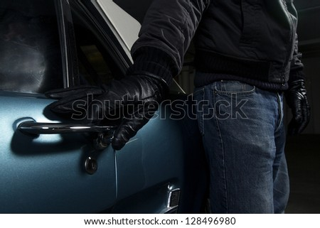 man trying to steal blue car - stock photo