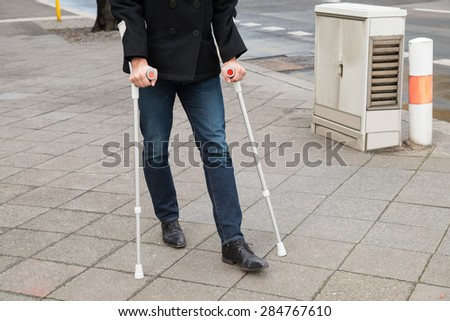 Man Trying To Walk On Street With The Help Crutches - stock photo