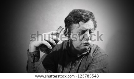 man turned away from the bottle of whiskey, which is held in the hand - stock photo