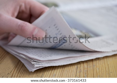 Man turning a page of a newspaper on a wooden table, focus on paper