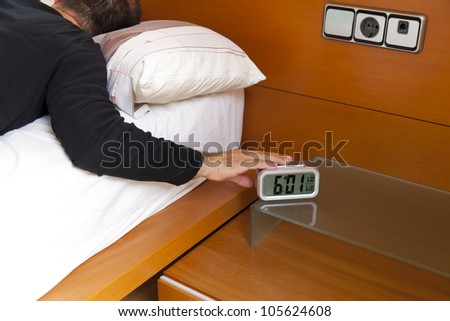 Man turning off the alarm clock at 6 o'clock in the morning - stock photo