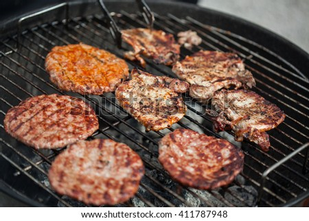 Man turning stakes and burgers on a BBQ oven. - stock photo