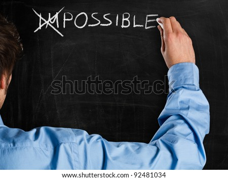 "Man turning the word ""Impossible"" into ""Possible"" - stock photo"