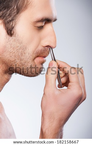 Man tweezing hair from nose. Side view of young man tweezing hair from nose and keeping eyes closed while standing against grey background