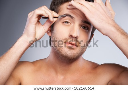 Man tweezing his eyebrows. Handsome young man tweezing his eyebrows and looking at camera while standing isolated on grey background - stock photo