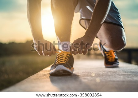 Man tying jogging shoes.A person running outdoors on a sunny day.Focus on a side view of two human hands reaching down to a athletic shoe. - stock photo