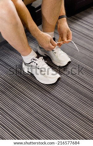 Man tying shoelaces of running shoes