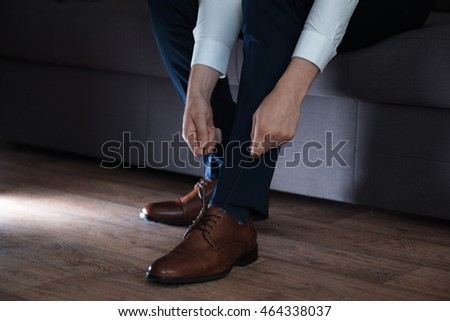 Man tying shoelaces on shoes