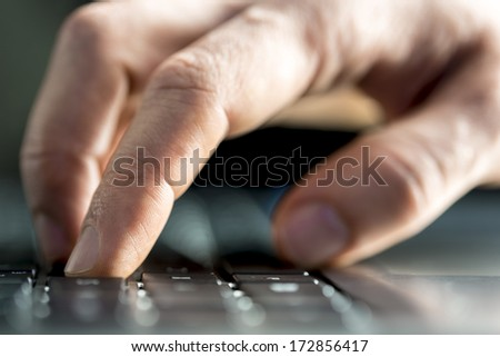 Man typing on a laptop computer inputting data or surfing the internet with a low angle closeup view with shallow dof of his finger depressing a key on the keyboard