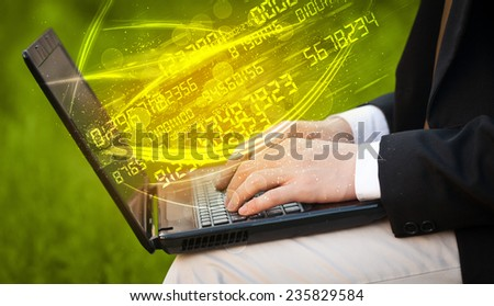Man typing on modern notebook with future number technology data coming out - stock photo