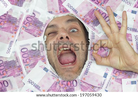 man under a bed of euro notes showing Ok gesture - stock photo