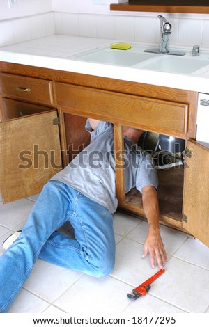Man under kitchen sink reaching pipe stock photo edit now man under kitchen sink reaching for pipe wrench do it yourself home repair solutioingenieria Gallery