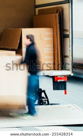Man unloading boxes from truck by hand in the middle of a street - fast shipment goods delivery - stock photo