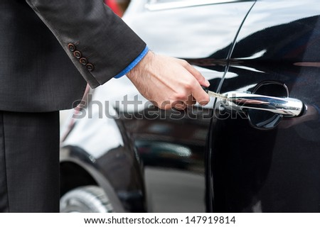 Man unlocking the door of his car, cropped image - stock photo
