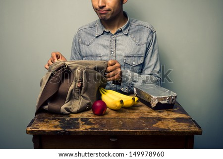 Man unpacking his lunch at old desk - stock photo