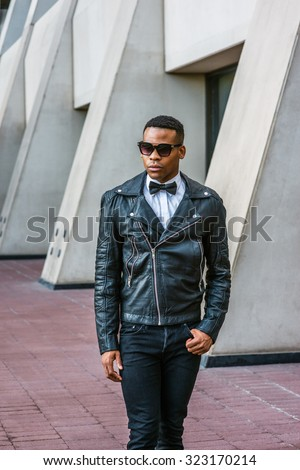 Man Urban Autumn/Spring Casual Fashion. Wearing black leather jacket, black jeans, sunglasses, white undershirt, black bow tie, a young African American guy walking on street in New York. City Boy.  - stock photo
