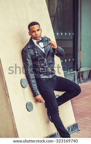 Man Urban Autumn/Spring Casual Fashion. Wearing black leather jacket, jeans, white undershirt, bow tie, holding sunglasses, a young African American guy leaning against wall on street in New York.  - stock photo