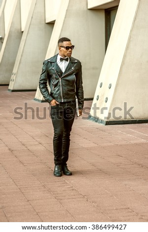 Man Urban Autumn/Spring Casual Fashion. Wearing black leather jacket, white undershirt, black bow tie, jeans, sunglasses, carrying laptop computer, African American guy walking on street in New York.