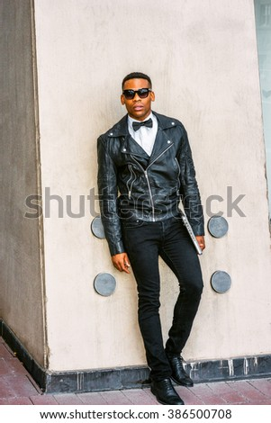 Man Urban Autumn/Spring Casual Fashion. Wearing black leather jacket, white undershirt, black bow tie, jeans, sunglasses, carrying laptop computer, African American guy standing on street in New York. - stock photo
