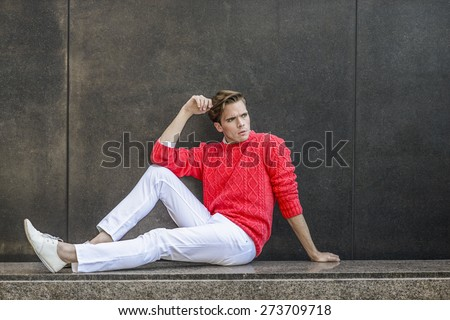 Man Urban Casual Fashion. Young blonde professional, wearing red sweater, white pant, casual fashion shoes, bending a leg and a arm, sitting on a marble bench, against the wall, relaxing, thinking. - stock photo