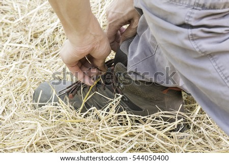 Man use hand to tie a boot shoe lace on the leaf, hay, bale, thatch, grass to be ready for work, business, training, trip, travel.