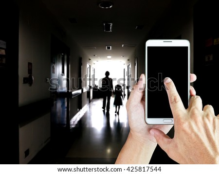 Man use mobile phone, blur image of a mother and daughter walking on the dark corridor in the hospital as background. - stock photo