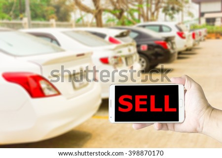 Man use mobile phone, blur image of automobile dealers-used cars as background.