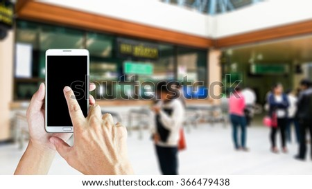 Man use mobile phone, blur image of counter in hospital as background. - stock photo