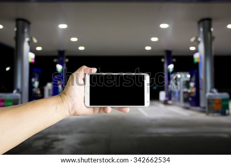 Man use mobile phone ,blur image of gas station as background. - stock photo