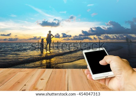 Man use mobile phone, blur image of sunset on the beach in Phuket, Thailand as background.