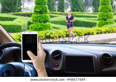 Man use mobile phone in the car, blur the beautiful green road as background.