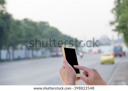 Man use mobile phone waiting for the bus with blurred Traffic background - stock photo