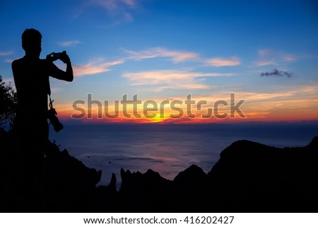 Man use phone to take photo of sunset on the mountain.