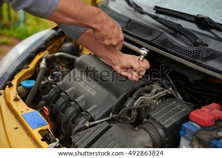 Man use wrench to repair the yellow car.