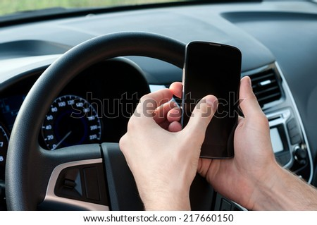 Man uses a phone in a car - stock photo