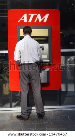 man uses atm - stock photo