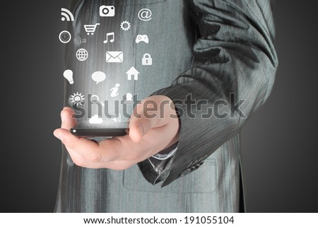 Man uses smart phone with icons on digital background - stock photo