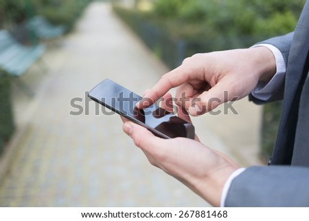 Man using a cell phone in park. close-up hands - stock photo