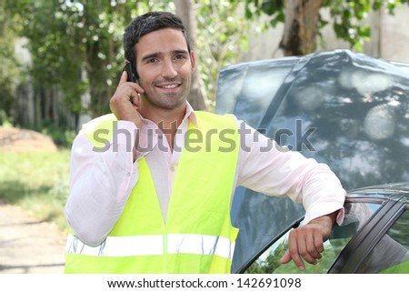Man using a cellphone at a vehicle breakdown - stock photo