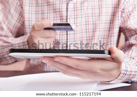 Man using a digital tablet for online buying - stock photo