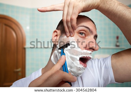 Man using a disposable razor to shave his beard off - stock photo