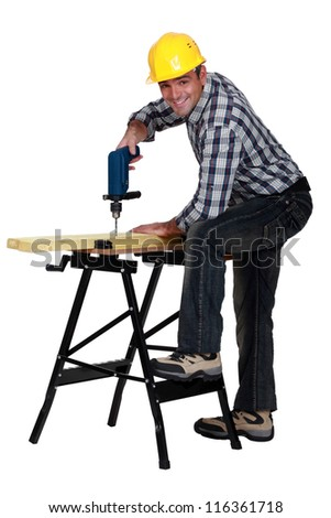 Man using a drill at a workbench - stock photo