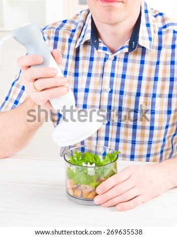Man using a hand blender to make a pate - stock photo