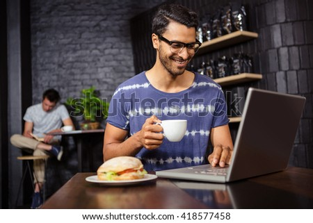 Man using a laptop and drinking coffee in a coffee shop - stock photo